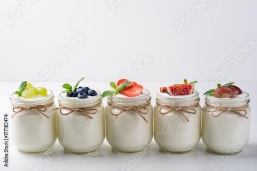 Plakat Świeży jogurt z jagodami w szklanych słojach. Zdrowa żywność, diety i koncepcja śniadanie. Skopiuj miejsce
