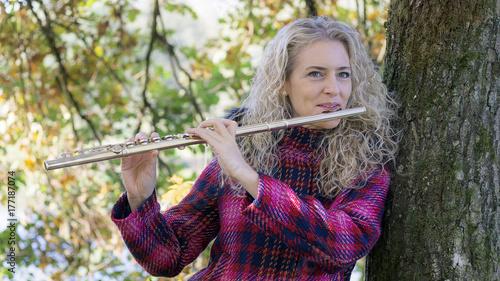 Obraz na PCV (fotoboard) Młoda kobieta gra na flecie.