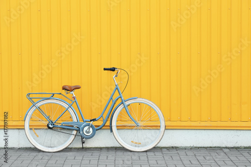 Retro bicycle near yellow wall outdoors