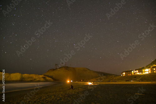 Fototapeta Ognisko na plaży z gwiazdami i przylądkiem Kiwanda w tle