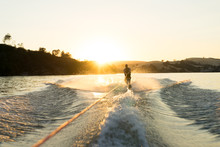 A Water Skier Takes A Run At Sunset On A Empty Glassy Lake