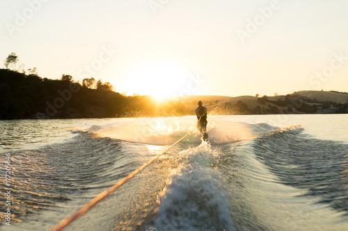 Plakat Narciarz wodny wykonuje bieg o zachodzie słońca na pustym jeziorze szklisty