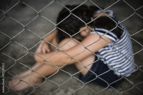 Fotografia, Obraz  Blurred sad girl child hug her knee, while sitting alone in cage was imprisoned