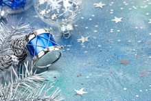 Shiny Blue Drum With Silver Fir-tree Branches And Cones On Blue Background With Star Confetti