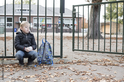 School boy forgotten by mother alone at school gate Canvas Print