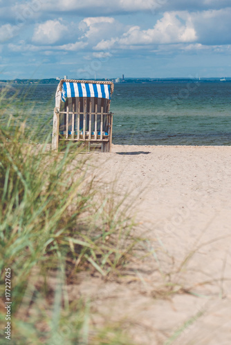 Spoed Foto op Canvas Noordzee Blue colored roofed chairs on sandy beach in Travemunde. Grass bush in foreground. Germany