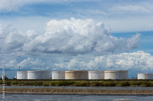 Foto op Plexiglas Stadion Oil tanks in a row under blue sky, Large white industrial tank for petrol, oil refinery plant. Energy and power