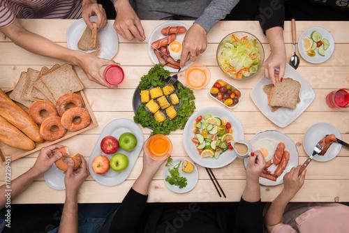Plakat Cieszyć się kolacją z przyjaciółmi. Odgórny widok grupa ludzi ma gościa restauracji wpólnie podczas gdy siedzący przy drewnianym stołem