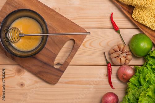 Plakat Natychmiastowi kluski dla gotować i jedzą w naczyniu z batożącym jajkiem i warzywami na drewnianym tle.
