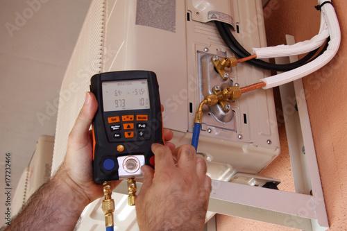 Photo Instalador verificando el compresor de aire acondicionado