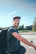 Side view portrait of happy man carrying backpack while riding bicycle on street against sky