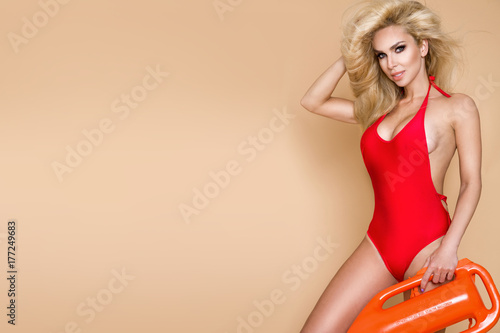 Sexy lifeguard with long blonde hair, standing in bikini with rescue board Canvas Print