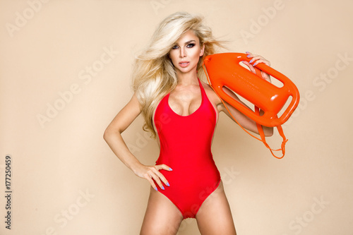 Sexy lifeguard with long blonde hair, standing in bikini with rescue board Wallpaper Mural