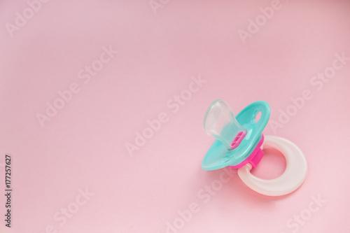 Valokuvatapetti Baby Pacifier mint blue on pink background closeup