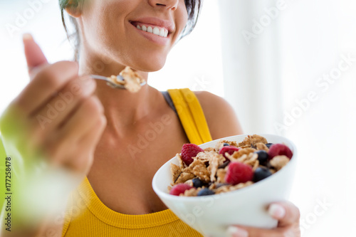 Beautiful young woman eating cereals and fruits at home. Fototapeta
