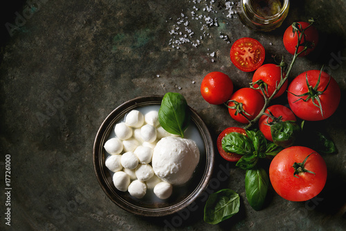 Fototapeta Ingredients for italian caprese salad. Mozzarella balls, buffalo in metal vintage plate, tomatoes, basil leaves, olive oil with vinegar over dark background. Top view with space. Rustic style obraz