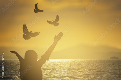 silhouette young women were  praying and free bird fly over blurred nature sunset background Wallpaper Mural