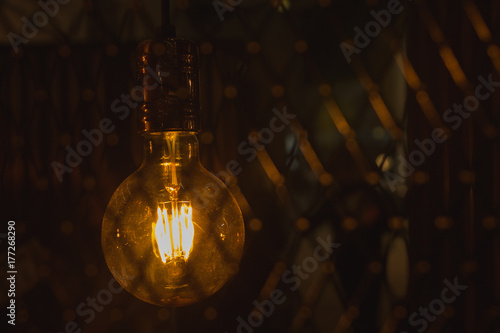 A glowing light bulb. Light bulb on a dark background with copy space.