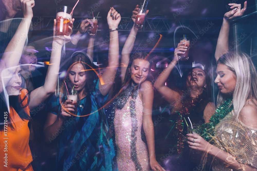 Fototapeta New Year dance party in night club. Happy friends company with drinks, Christmas celebration in motion. Disco people in blurred colors, modern youth life