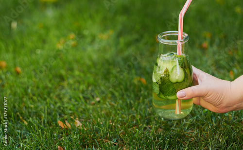 Healthy green detox drink on summer grass in hand. Fresh cold tea jar outdoors. Diet or healthy lifestyle concept