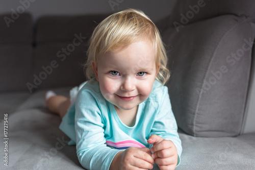 Little toddler girl portrait on the sofa Wallpaper Mural