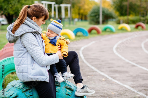 Young sporty woman and her infant son in warm clothes sitting on colorful tires on stadium track background. Motherhood, sport and lifestyle concept.