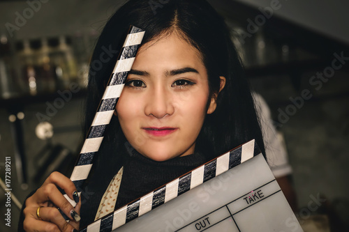 Asian actress holding slate film and expressing emotion to test the movie Wallpaper Mural