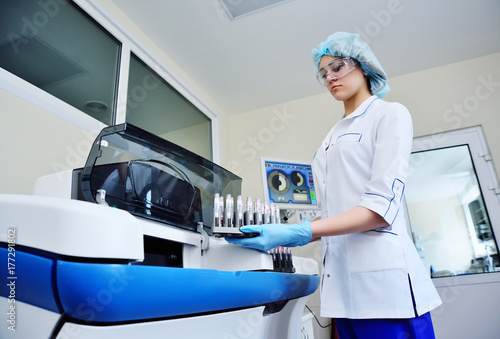 a female scientist near the analyzer in a medical microbiological laboratory Wallpaper Mural