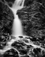 FototapetaVertical Black and White image of blurred water in a waterfall