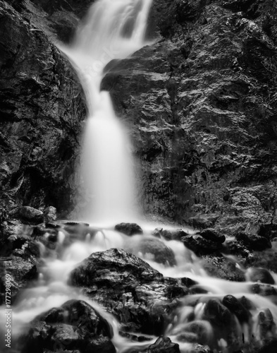 Vertical Black and White image of blurred water in a waterfall