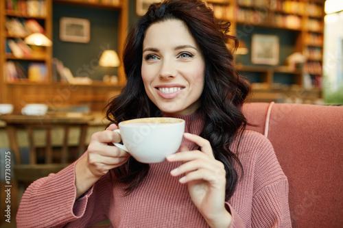 Plakat ładna kobieta pije kawę w kawiarni. Czas przyjemności