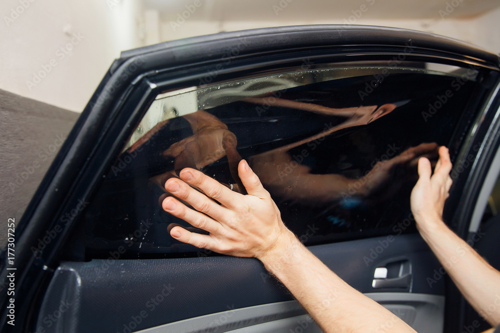 Fototapety, obrazy: Master installs a tint film for the car glass with a hairdryer and spatula with glare of light. Concept tinting car