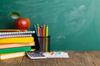 Back to school supplies. Books and blackboard on wooden background