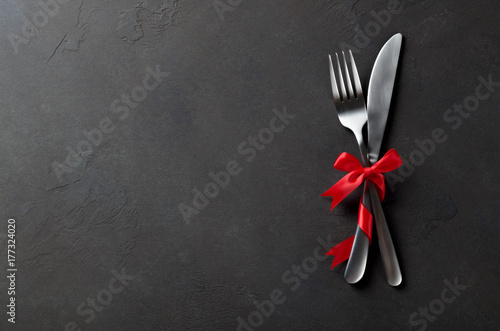 Festive set of cutlery knife and fork with red satin bow, dark stone slate background, top view, copyspace