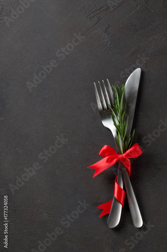 Festive set of cutlery knife and fork with red satin bow with rosemary, dark stone slate background, top view, copyspace, vertical image