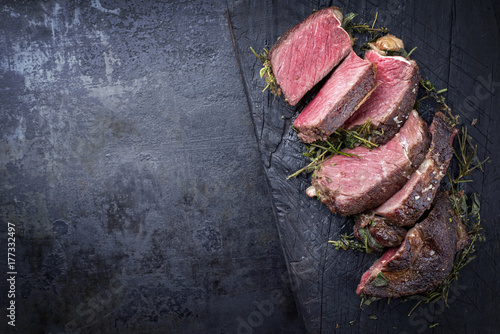 Barbecue dry aged Kobe rib eye steak as close-up on a burnt board with copy space left