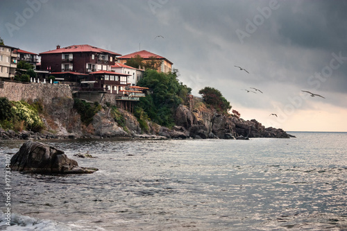 Foto auf Gartenposter Stadt am Wasser Coastal landscape - the rocky seashore with seagulls and houses, town of Sozopol on the Black Sea coast in Bulgaria