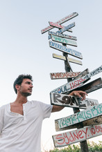 Young Man Next To A Signpost W...