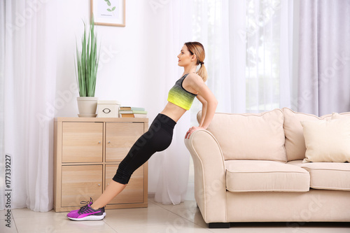 Foto auf Leinwand Gymnastik Young beautiful woman training at home