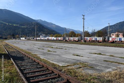 Fotobehang Treinstation Bahnhof, Ladezone, Ladebereich, Abstellgleis, Gleis, Schiene, Oberleitung, verwachsen, stillgelegt, Güterzug, Zug, Wagen, Güterwagen, Lienz, Osttirol
