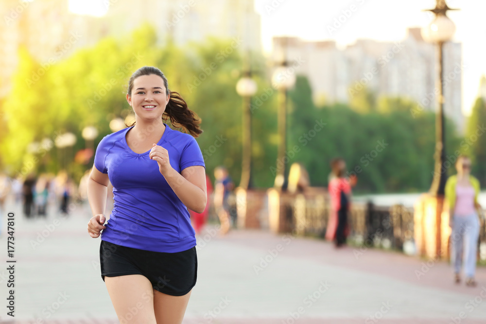 Fototapety, obrazy: Overweight young woman jogging in the street. Weight loss concept