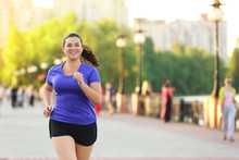 Overweight Young Woman Jogging...