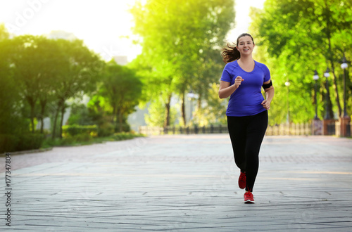 Foto  Overweight young woman jogging in park. Weight loss concept