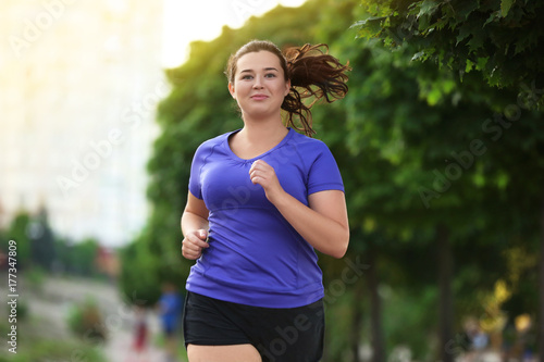 Overweight young woman jogging in the street. Weight loss concept Canvas Print