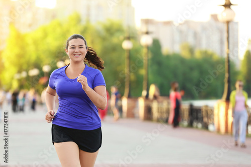 Poster Jogging Overweight young woman jogging in the street. Weight loss concept