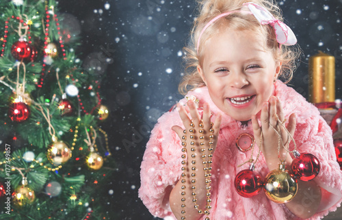 Zdjęcie XXL Śmieszna mała dziewczynka dekoruje choinki