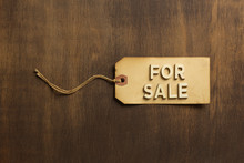 For Sale Written In Wooden Letters On A Paper Tag