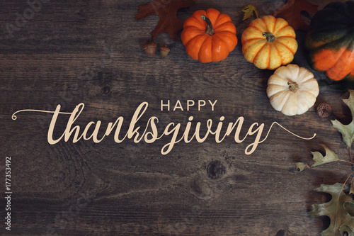 Fotografía  Happy Thanksgiving text with pumpkins and leaves over dark wood background