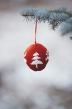 Red Christmas Ornament  Hanging In A Fir Tree