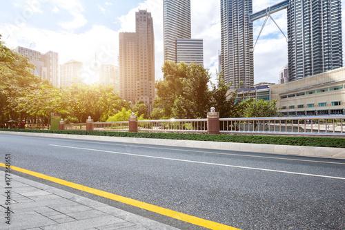 Fototapeta pusta asfaltowa droga i nowoczesne budynki w śródmieściu współczesnego miasta